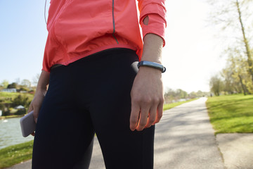 Woman With Activity Tracker And Cellphone Exercising
