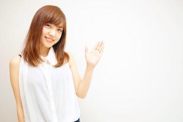 笑顔で指をさす若い女性 日本人 ポイント 指差し 女子 アピール セールスポイント