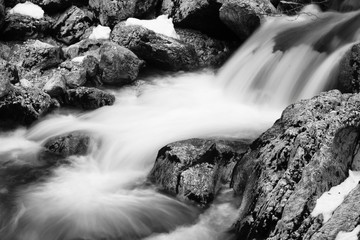 close-up of rocks in river brook in satin soft water flowing around in long exposure in black and white