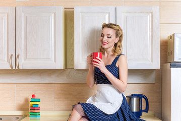 pretty  woman drinks tea in the kitchen. vintage style
