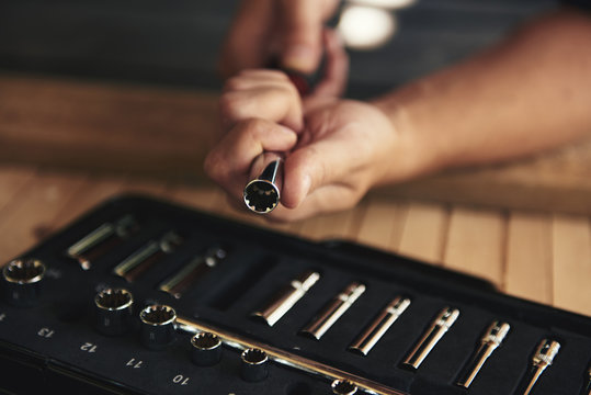 Close-up of mechanic hands changing socket wrench over toolbox. Concept of repair and diy.
