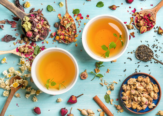 Two cups of healthy herbal tea with mint, cinnamon, dried rose and camomile flowers in spoons over blue background