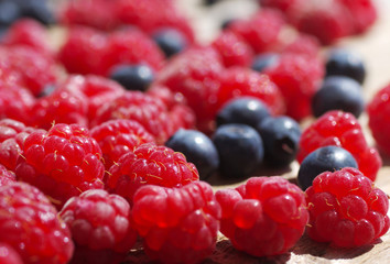 Juicy mature berries of  raspberry and bilberry  close up. Berry background