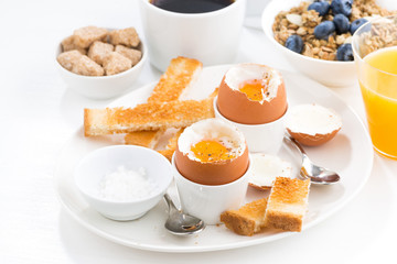 delicious breakfast with soft boiled eggs and crispy toasts