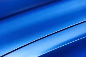Surface of blue sport sedan car metal hood, part of vehicle bodywork, steel gradient line pattern