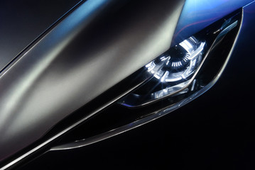 Predatory car headlight and hood of powerful sports grey car with blue glare on dark background