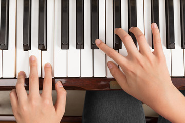 Top view close up of female hands playing piano