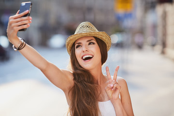 Portrait of attractive young woman taking selfie in the city mak