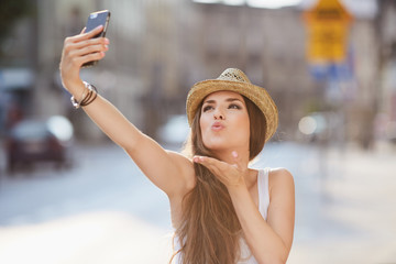 Young woman taking selfie, sending kiss on city street