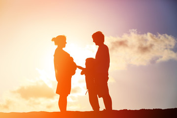 happy pregnant mother and father with son at sunset