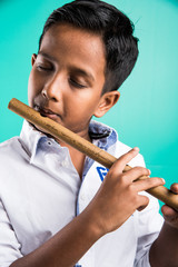 10 year old indian boy playing flute, indian boy and music, indian boy learning music, indian boy with musical instrument, brown indian boy