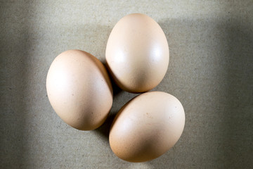 Three Fresh chicken eggs on a brown background.