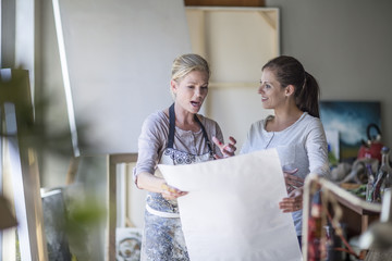 Female painter presenting painting in home studio