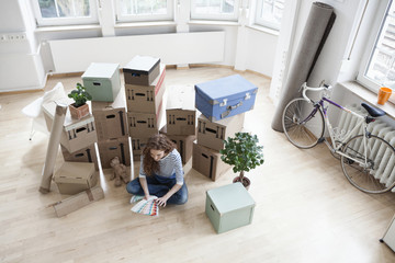 Woman surrounded by cardboard boxes with color samples on floor
