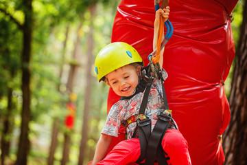 Little happy child boy in adventure park in safety equipment in