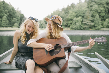 Cheerful Friends Having Fun Playing Music on a Rowboat