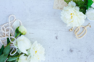 White fresh peony flowers and buds with pearls jewellery on aged white wooden table with copy space