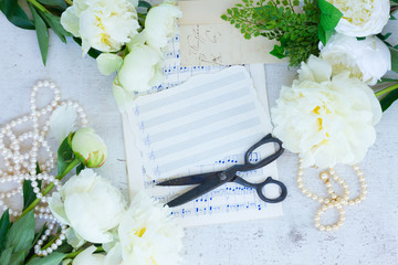 White fresh peony flowers vintage flat lay wedding frame with note paper