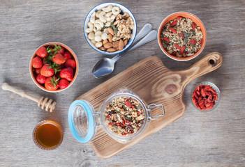 Grain free oat free paleo muesli, raw food: mixed nuts, seeds, goji berries, chia, honey and strawberries, selective focus on the muesli in the mason jar, top view