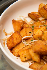 Potato Wedges with Rosemary and Herbs in white Bowl closeup
