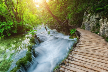 Tourist route on the wooden flooring along the waterfall at the Plitvice Lakes National Park, Croatia, nature sunny background