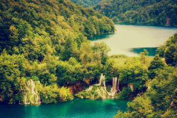 Amazing emerald lakes and waterfalls, surrounded by forests at Plitvice Lakes National Park, Croatia, nature vintage background suitable for wallpaper