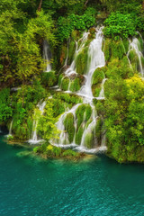 Picturesque waterfalls, surrounded by green trees and emerald lake, Plitvice Lakes National Park, Croatia, vertical nature background