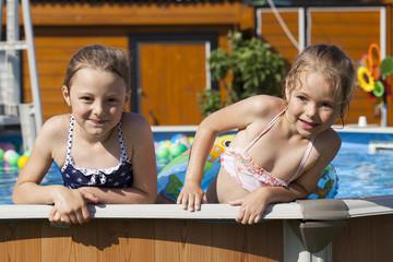 Two sisters in bikini swimming pool