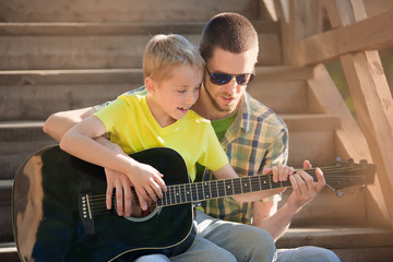 father learning his son to play guitar
