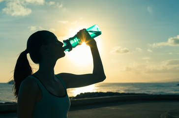 Female drinking a bottle of water on a hot summer day.