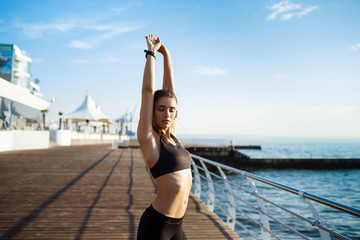 Picture of young beautiful fitness girl makes sport exercises with sea coast on background