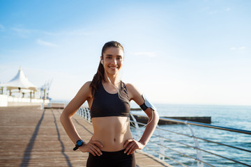 Picture of young fitness girl ready for sport exercises with sea coast on background