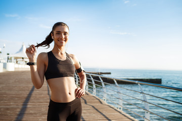 Picture of young smiling fitness girl ready for sport exercises with sea coast on background