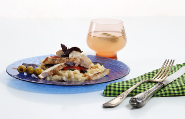 Traditional italian risotto with chicken, tomato, basil and parmesan on blue plate with knife and fork and glass of wine