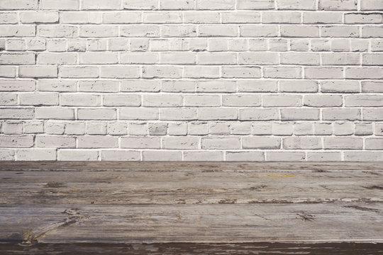 Empty wooden table over white brick wall. Background for product montage display