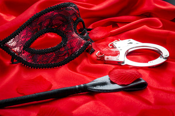 Fototapeta Concept image with a mask, hand cuffs and a flogger covered in rose petals on red silk. BDSM is a variety of erotic practices or role playing involving bondage, dominance and submission, masochism obraz