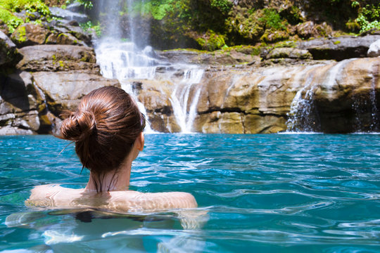 Beautiful woman enjoying bathing near natural waterfall.
