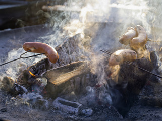 Finland, Helsinki, Tolo, Sausages cooking in bonfire