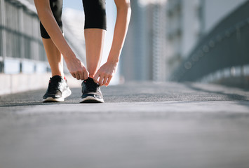 Getting ready for a run. Female runner tying her shoe. Wall mural