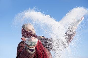 Sweden, Vastergotland, Tarby, Senior woman playing in snow