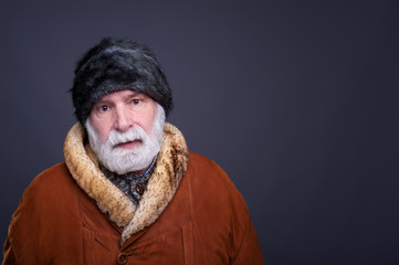 Senior man in winter outfit, studio shot.