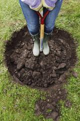 Sweden, Vasterbotten, Falktrasket, Woman holding shovel, low section
