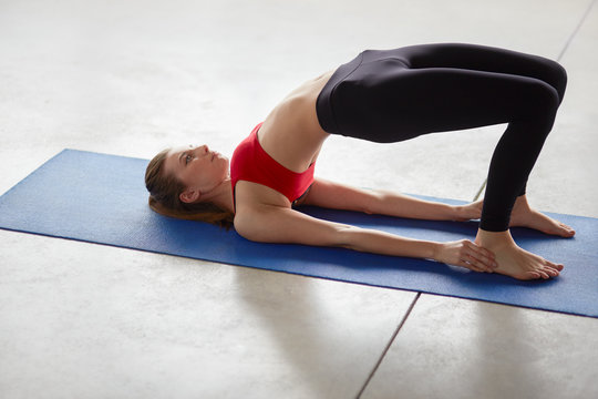 Side view of young woman doing half bridge pose