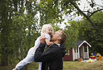 Sweden, Uppland, Father holding up daughter (4-5)