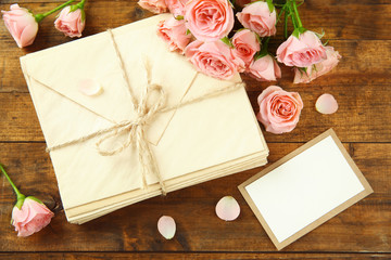 Fresh roses and present on wooden background