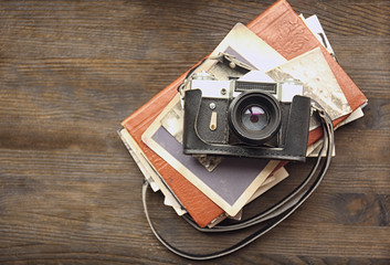 Album with vintage photos and camera on wooden background