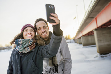 Sweden, Vasterbotten, Umea, Young couple taking selfie by bridge in winter