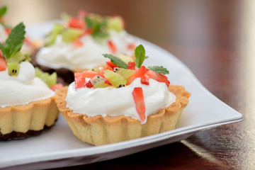 Tarts with whipped cream and strawberries and mint leaves