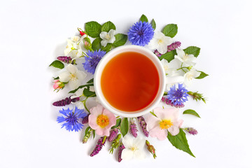 Cup of tea with fresh flowers lying around on white background