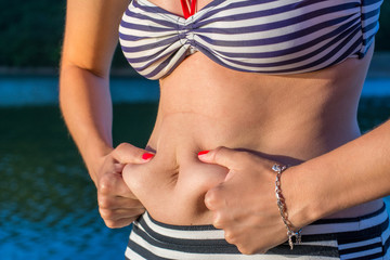 Woman measuring stomach fat on summer vacation